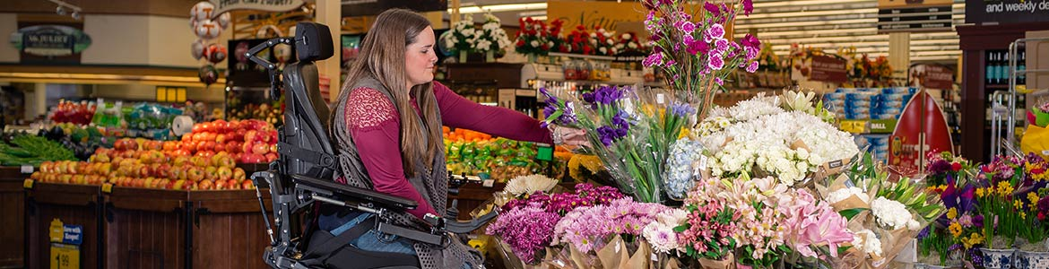 Girl in a wheelchair looking at flowers in a grocery store.